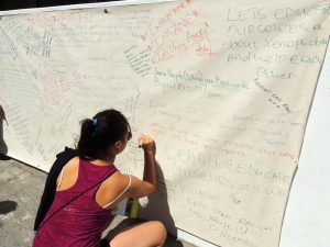 Hannah signing a poster promoting unity among Africans
